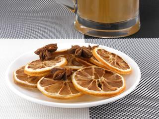 beer mug with cinnamon and lemon on white plate
