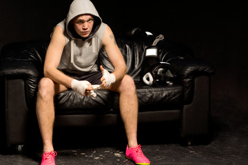 Young boxer sitting thinking and waiting