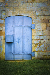 Old blue metal door set in stone