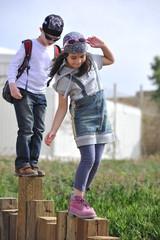 Children walk on wooden logs