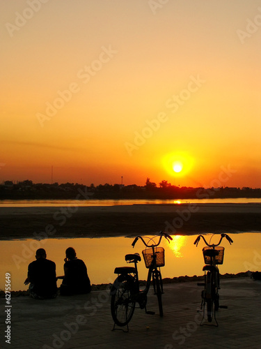 Silhouetted couple watching sunset at Mekong river waterfront, V