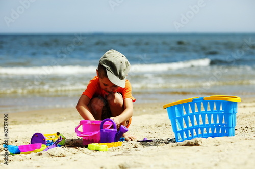 boy playing toys on beach