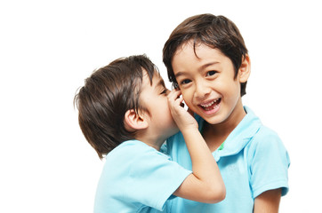 Little sibling boys sharing a secret on white background