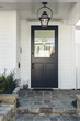 Black front door of white home