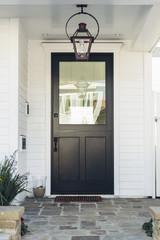 Black front door of white home