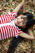 Pretty little asian girl laying on the leafs