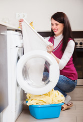 woman looking white clothes near washing machine