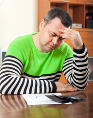 frustrated man at  table with  wallet and documents