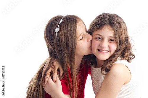 Two sisters kissing and hugging isolated on white..