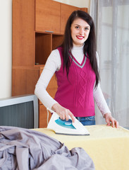 Happy  housewife ironing with iron