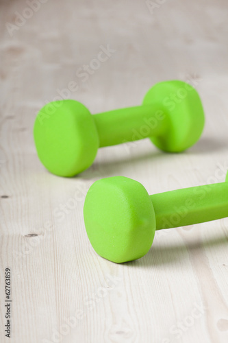 small green dumbbells on wooden surface