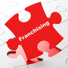 Finance concept: Franchising on puzzle background