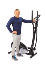 Young man uses elliptical cross trainer.