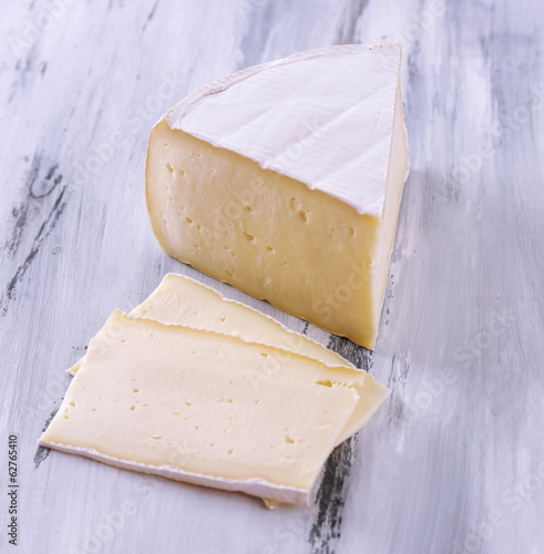 Tasty Camembert cheese, on wooden table