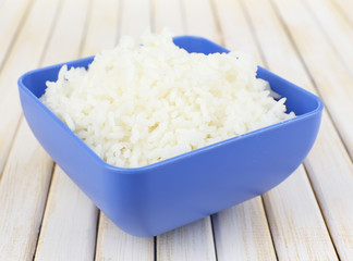 Cooked rice in bowl on wooden background