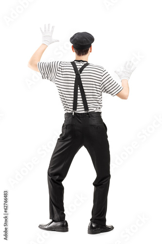 Full length portrait of a mime artist performing