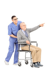 Senior in a wheelchair pointing with finger