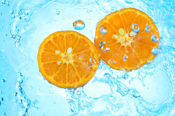pouring water in two organic tangerines halfs