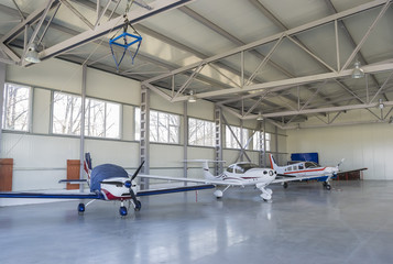 Three light airplanes stationed in an air dock
