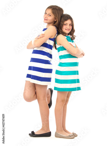 Playful sisters standing back-to-back isolated on white..