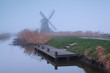 windmill by river in dense fog