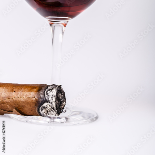 Beautiful cognac with cuban cigar on white background