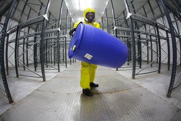 technician in protective  uniform with blue barrel