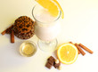 Eggnog with spices and orange on yellow background
