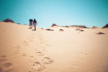 couple climbing sand dunes