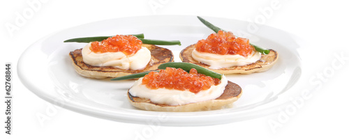 Pancakes with red caviar on plate, isolated on white