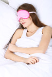 Young beautiful woman sleeping in bed with eye mask close-up
