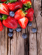 Fresh berries on wooden background, strawberry and blueberry fru