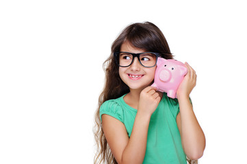 girl wearing glasses holding piggy bank at her ear