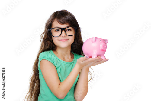 schoolgirl wearing glasses holding piggy bank