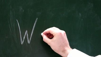 Eine Männerhand schreibt Warum auf eine Tafel