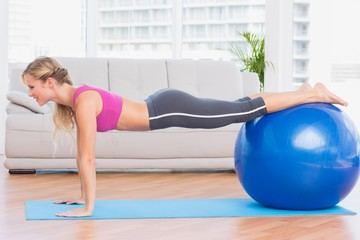 Slim blonde in plank position using exercise ball