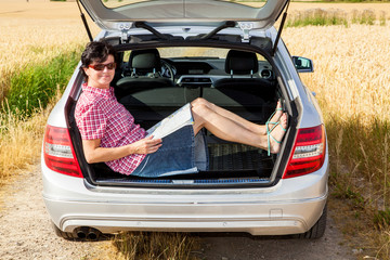 Woman sitting in the trunk of her car