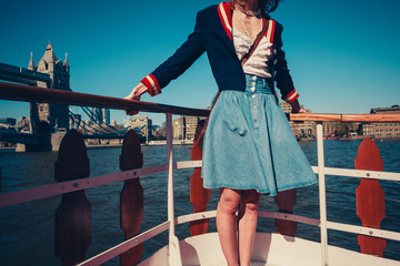 Young woman on the deck of ship with skirt blowing in the wind
