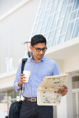 indian business man with coffee and papers outside his office