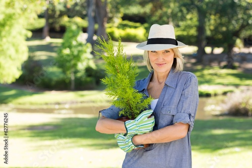 Woman holding pot plant in garden