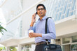 indian business man with smart phone with office background