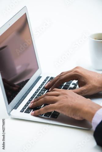dark skinned male with a cup of coffee and laptop, high key phot