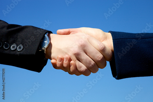 Hand shake between man and woman in front of the sky