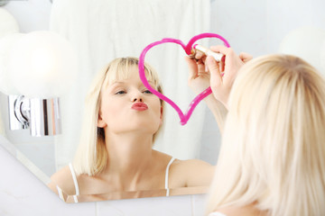 Young woman drawing big heart on mirror.