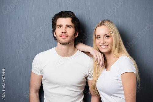 glückliches junges paar vor grauer wand