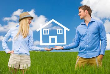 Pärchen im Feld mit Händen hält Haus in der Luft