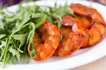 Fried spicy shrimp, prawn and salad of arugula, rukkola