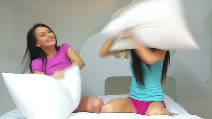 Two lesbian women at pillow fights in bed.