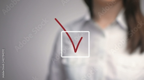 woman hand writing a checkmark focus on foreground