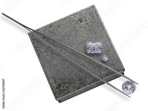 diamonds and tweezers on a jeweler anvil